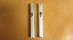 Metal mezuzah case on the left withstandard screw holes, right with enlarged screw holes for self drilling screws to be used on heavy steel door frames