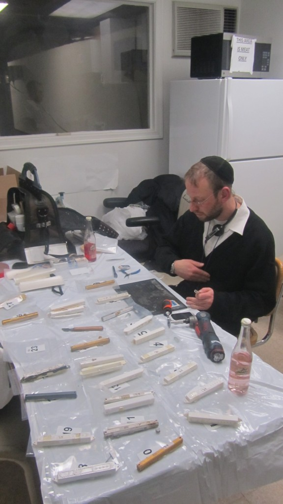 Melech Michaels at work checking the mezuzos in a small side room of the factory.